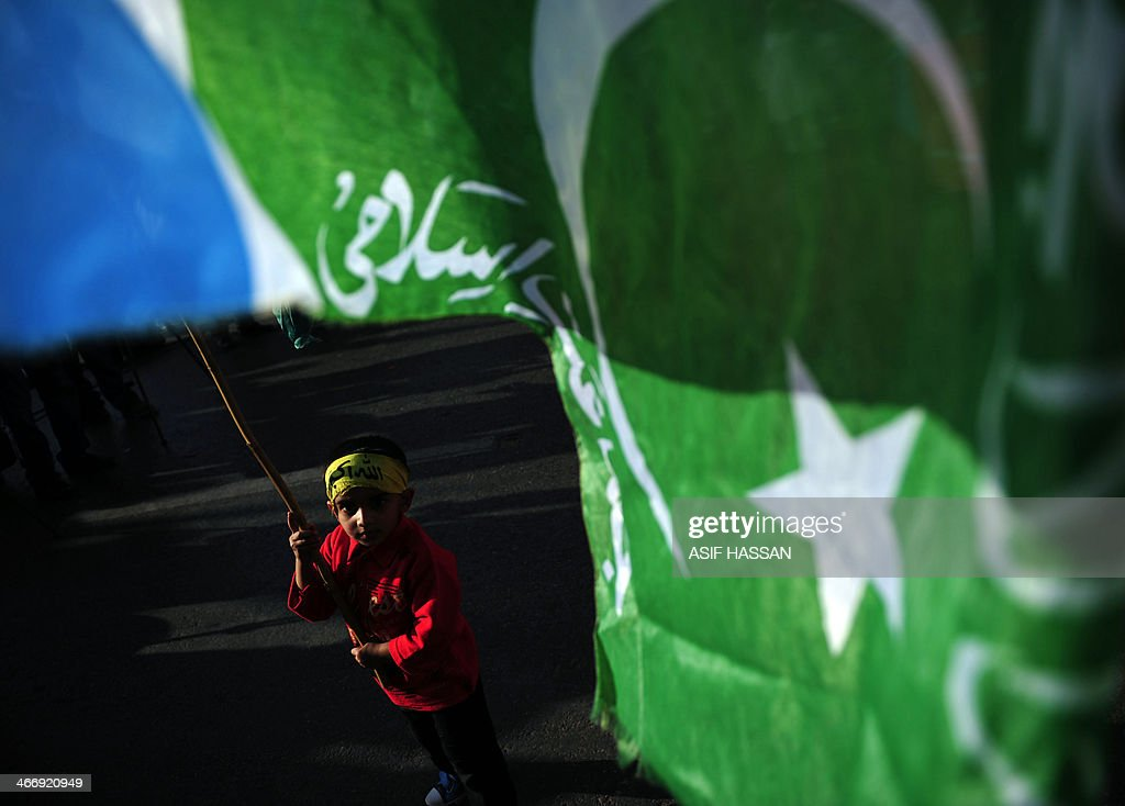 A Pakistani child waves a flag of the fundamentalist Islamic political party Jamaat-i-Islami (JI) during the Kashmir Solidarity Day rally in Karachi on February 5, 2014. Hundreds of people rallied across Pakistan to denounce Indian rule in Kashmir, the disputed Muslim-majority Himalayan state divided between divided between India and Pakistan. AFP PHOTO/Asif HASSAN