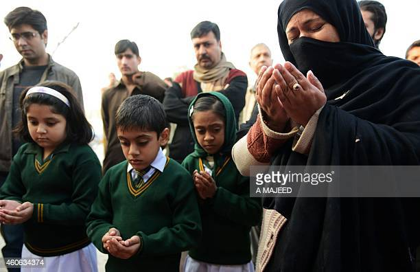 Pakistani children and mourners pray for the children and teachers killed in an attack by Taliban militants outside the armyrun school where the...