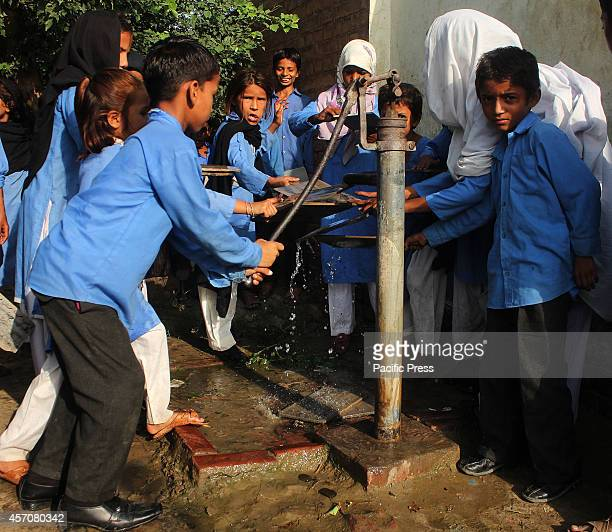 Pakistani children fetch water from a pump and pursue their studies even without the modern facilities in a village near Wagah border area in the eve...