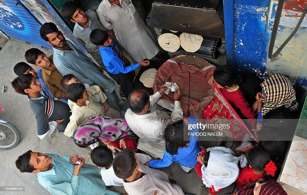 Pakistani children gather around a man making wheat bread at his shop in Rawalpindi on October 19, 2012. Net foreign investment in Pakistan plummeted by 67 percent in the first quarter, according to official data, with experts blaming the fall on poor economic management, energy shortages and persistent terrorism. AFP PHOTO/Farooq NAEEM