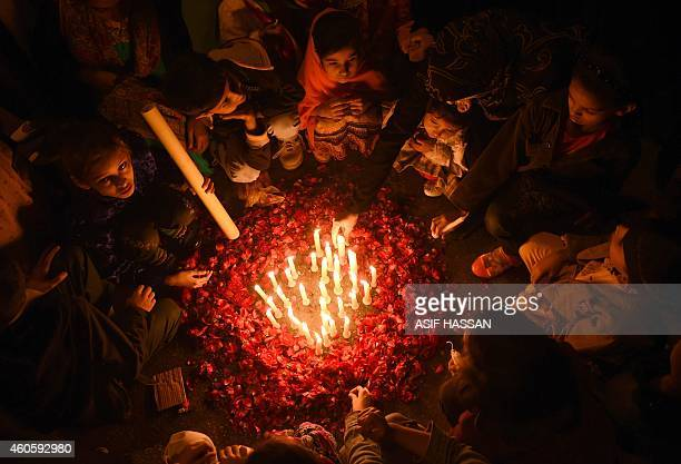 Pakistani children gather around lit candles for the victims of an attack by Taliban gunmen on an armyrun school in Peshawar in Karachi on December...