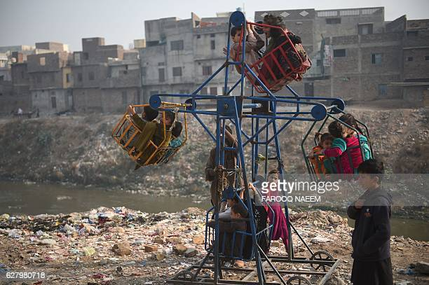 TOPSHOT Pakistani children play on a swing in a neighbourhood in Rawalpindi on December 6 2016 / AFP / FAROOQ NAEEM