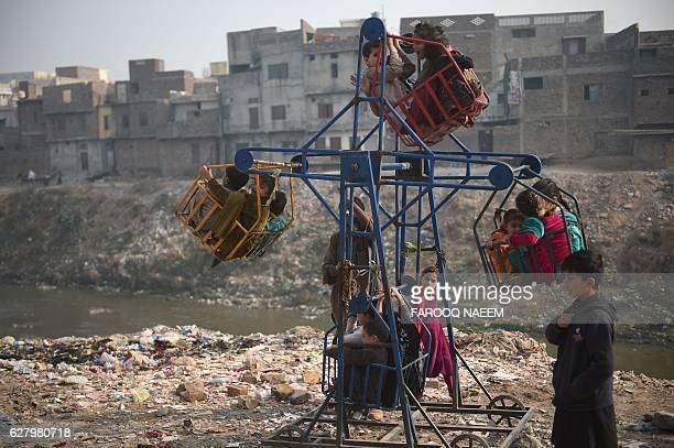 TOPSHOT Pakistani children play on a swing in a neighbourhood in Rawalpindi on December 6 2016 / AFP / FAROOQ NAEEM