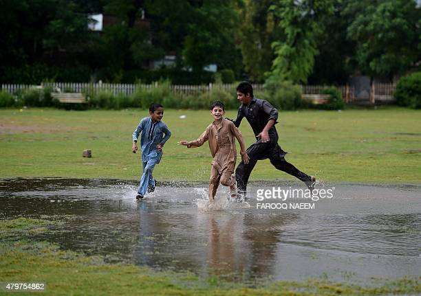Pakistani children run through a puddle at a park during monsoon rain in Islamabad on July 7 2015 AFP PHOTO / Farooq NAEEM