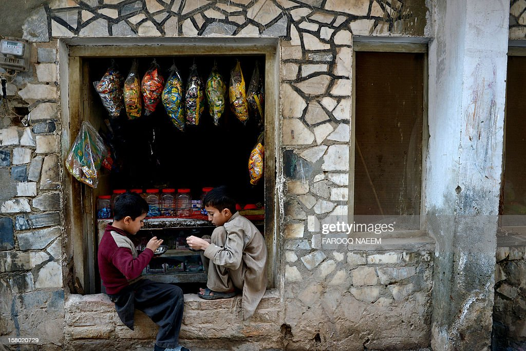 Pakistani children sit in front of a shop in Rawalpindi on December 9, 2012. Pakistan's growth remains too weak, underlying inflation is high and the trade balance is heading in the wrong direction, the IMF said in a statement. AFP PHOTO/Farooq NAEEM