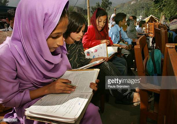 Pakistani children start their first day of class in a makeshift school along the road in a tent city October 27 2005 in Muzaffarabad Pakistan...