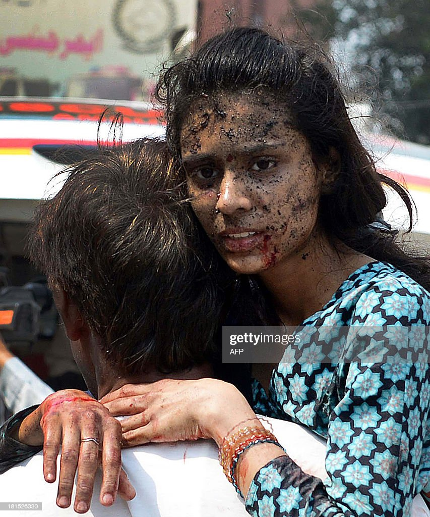 A Pakistani Christian carries an injured woman on her arrival at the hospital after two suicide bomb attacks on a Church in Peshawar on September 22, 2013. Two suicide bombers killed at least 53 people and wounded more than 100 in an attack on a church service in the restive northwestern Pakistani city of Peshawar, officials said.