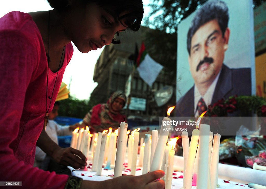 A Pakistani Christian girl lights candles in front of the picture of slain Christian minister Shahbaz Bhatti in Karachi on March 6 2011 Bhatti an...