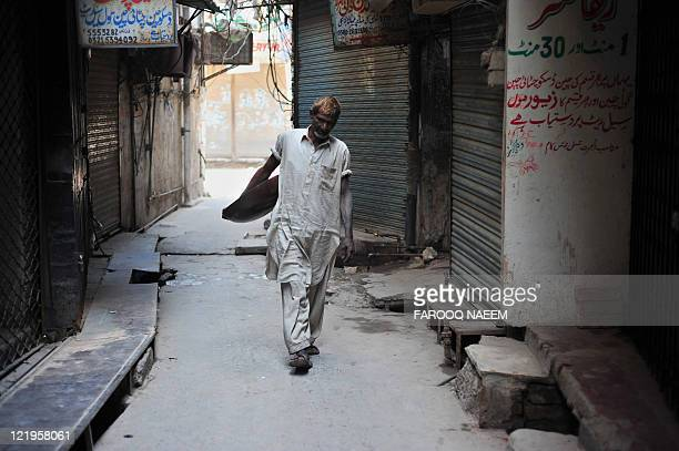 Pakistani christian Hameed walks through a gold market while scavenging for gold in the drainage's in Rawalpindi on August 19 2011 The price of gold...