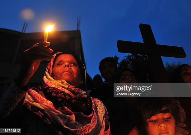Pakistani Christian protesters hold candle vigil as they take part in a demonstration to pay respect to the victims of the Peshawar suicide attacks...