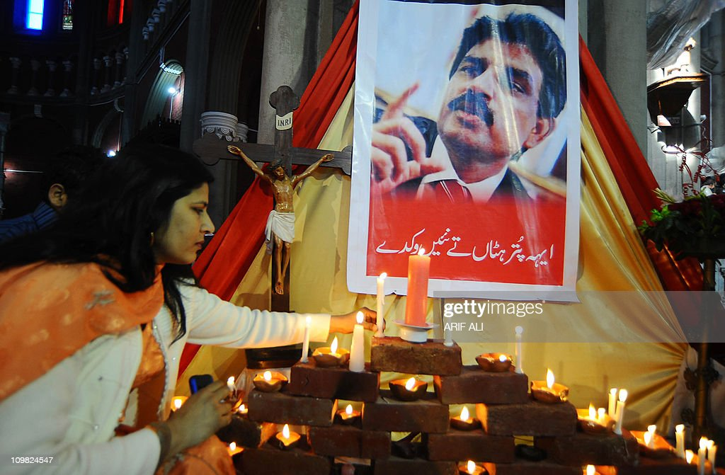 A Pakistani Christian woman lights candles in front of a picture of slain Christian minister Shahbaz Bhatti at The Heart Cathedral Church in Lahore on March 6, 2011. Bhatti, who was an outspoken campaigner against Pakistan's Islamic blasphemy laws, died in a hail of bullets on March 2, as he left his mother's home in the Pakistani capital Islamabad. AFP PHOTO/Arif ALI