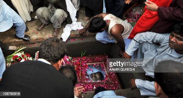 Pakistani Christians bury the coffin of slain their leader and minister for minorities Shahbaz Bhatti in the family graveyard in his native village...