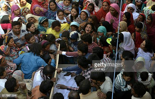 Pakistani Christians gather around an opened coffin as they mourn the death of a blast victim of the March 27 suicide bombing in Lahore on March 28...