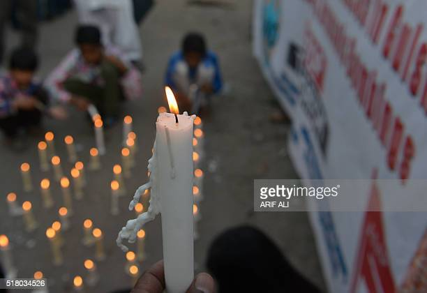 Pakistani Christians hold lighted candles as they stage a rally in Lahore on March 29 to pay tribute for the victims of a suicide bomb blast Taliban...