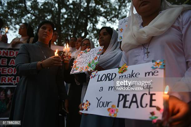 Pakistani Christians hold placards and lighted candles as they stage a rally in Lahore on March 28 for victims of a suicide bomb blast Pakistan's...