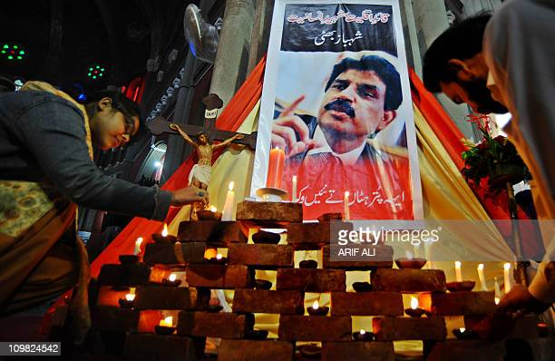 Pakistani Christians light candles in front of a picture of slain Christian minister Shahbaz Bhatti at The Heart Cathedral Church in Lahore on March...