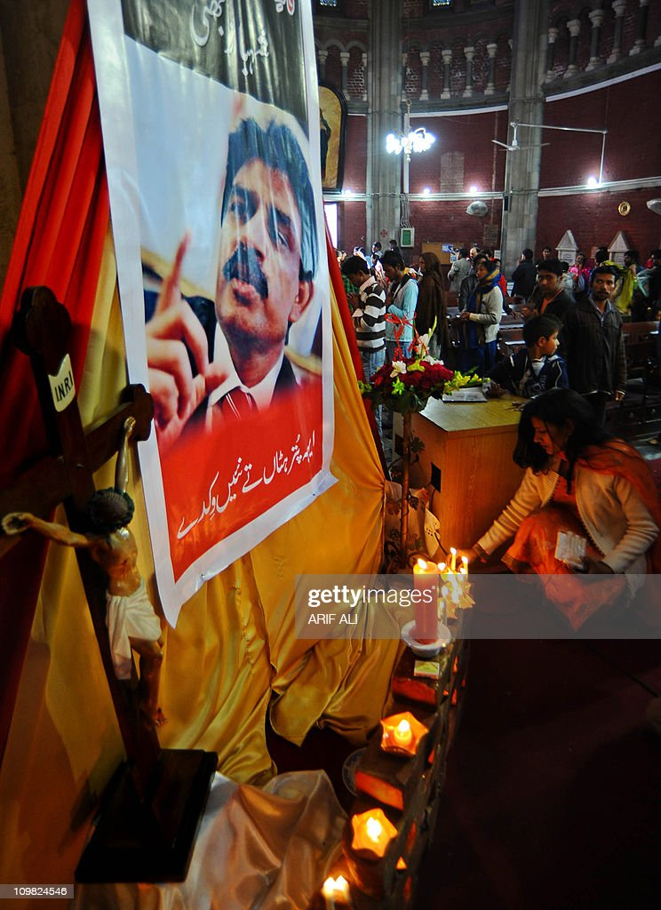Pakistani Christians light candles in front of a picture of slain Christian minister Shahbaz Bhatti at The Heart Cathedral Church in Lahore on March 6, 2011. Bhatti, who was an outspoken campaigner against Pakistan's Islamic blasphemy laws, died in a hail of bullets on March 2, as he left his mother's home in the capital Islamabad. AFP PHOTO/Arif ALI