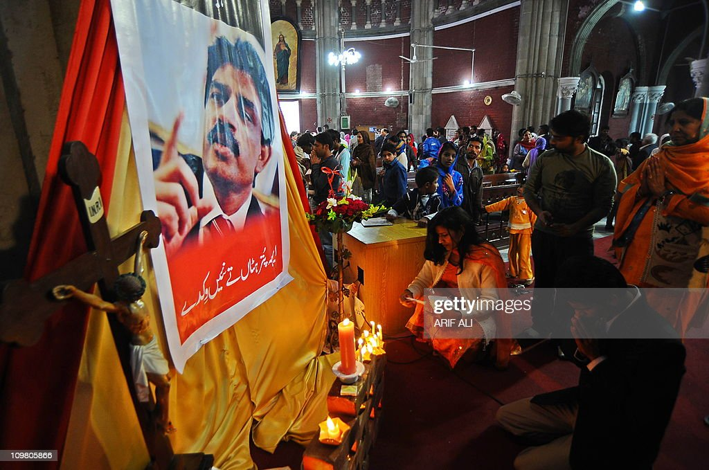 Pakistani Christians light candles in front of a portrait of slain Pakistan's Christian minister Shahbaz Bhatti at the Heart Cathedral Church in Lahore on March 6, 2011. Bhatti, 42, an outspoken campaigner against Pakistan's Islamic blasphemy laws, died in a hail of bullets as he left his mother's home in the capital Islamabad on March 2. AFP PHOTO/Arif ALI