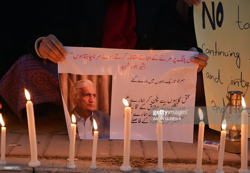 A Pakistani civil society activist holds a placard during a vigil for slain Pakistani provincial minister Bashir Bilour in Islamabad on December 24, 2012. Bilour, senior minister of northwestern Khyber Pakhtunkhwa province, was killed along with eight other people when the suicide bomber struck at a political meeting in the provincial capital Peshawar on December 22, 2012. AFP PHOTO/Aamir QURESHI