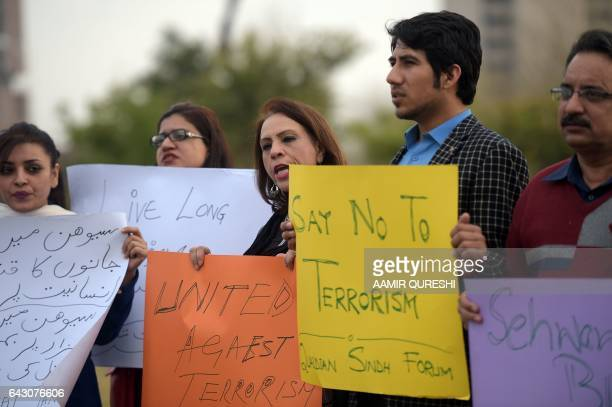 Pakistani civil society activists carry placards as they shout slogans during a peace protest in Islamabad on February 20 following a deadly bomb...