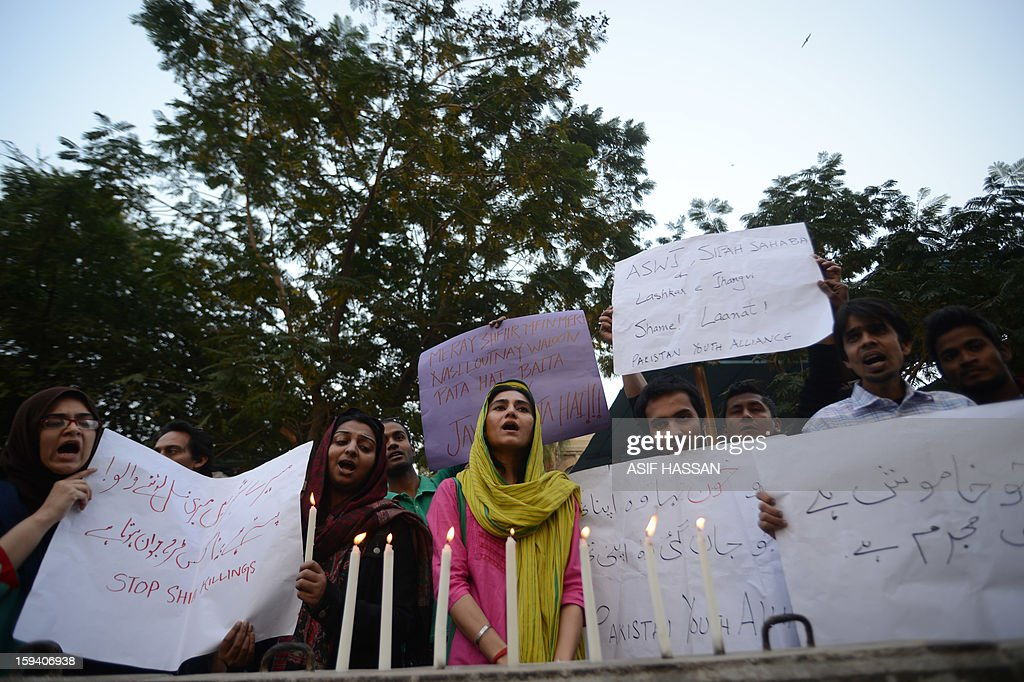 Pakistani civil society activists light candles and chat slogans against the twin bombings attack in Quetta, in Karachi on January 2013. Pakistan's Prime Minister Raja Pervez Ashraf arrived in the southwestern city of Quetta to meet Shiite Muslim families refusing to bury their dead after devastating bombings, officials said. AFP PHOTO/Asif HASSAN