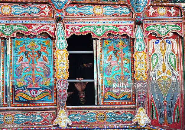 A Pakistani cleaner dusts a deccorated mini passenger bus in Karachi on September 18 2013 Bus art has been very much in vogue in this port city and...