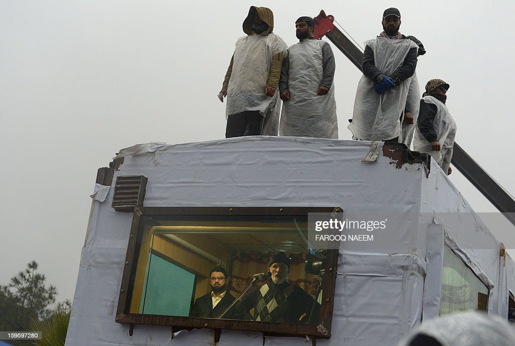 Pakistani cleric Tahir-ul Qadri (C-below) addresses his supporters from his makeshift room at a protest rally in Islamabad on January 17, 2013. A populist Pakistani cleric calling for electoral reforms announced that a mass sit-in of tens of thousands of people camped outside parliament in Islamabad would end January 17. AFP PHOTO/Farooq NAEEM