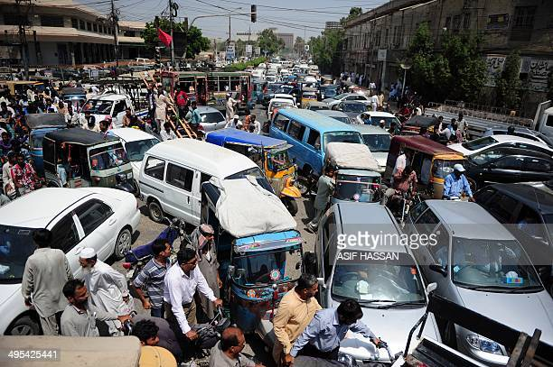 Pakistani commuters are stuck in a traffic jam in Karachi on June 3 2014 following the arrest of Altaf Hussain head of Pakistan's Muttahida Qaumi...