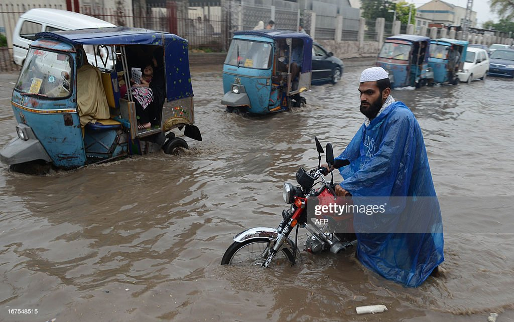 Pakistani commuters cross a flooded street following heavy rain in Peshawar on April 26, 2013. Pakistan has suffered devastating monsoon floods for the last three years, including the worst in its history in 2010 when catastrophic inundations killed almost 1,800 people and affected 21 million.