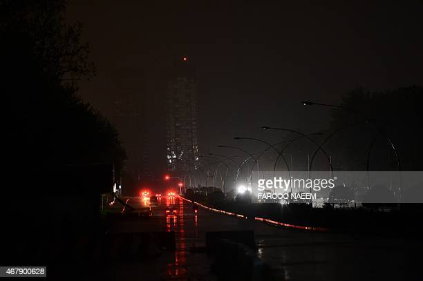 Pakistani commuters drive along a darkened constitution avenue in Islamabad on March 28 during 'Earth Hour' Millions are expected to take part around...