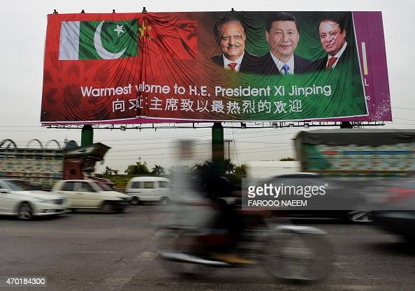 Pakistani commuters drive past a welcoming billboard featuring pictures of visiting Chinese President Xi Jinping and his Pakistani counterpart...