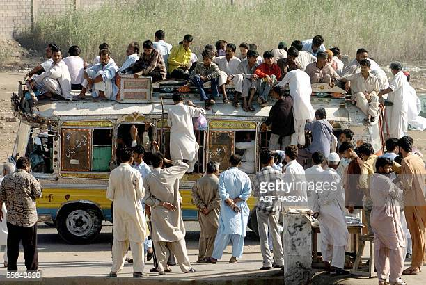 Pakistani commuters rush towards a mini bus in a bid to find space on its rooftop at a busy street in Karachi 04 October 2005 Public buses remained...