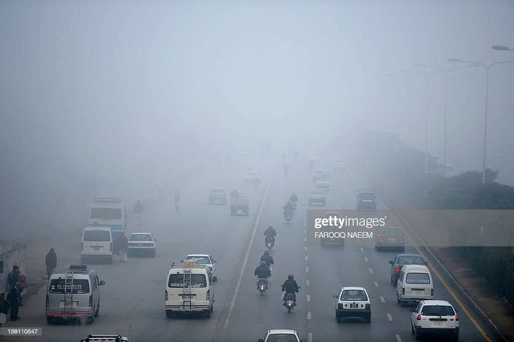 Pakistani commuters travel on an express way during a foggy morning in Islamabad on January 8, 2012. The fog has also disrupted flight schedule at the Islamabad airport and four Islamabad-bound flights from Dubai and Afghanistan were diverted to Lahore. AFP PHOTO/Farooq NAEEM