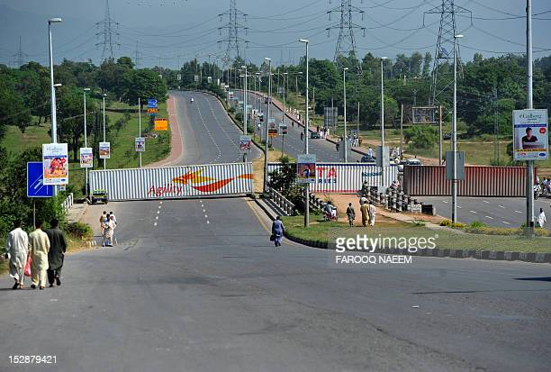 Pakistani commuters walk on a road linked to the US embassy that was blocked with containers to help prevent any possible protests against an...