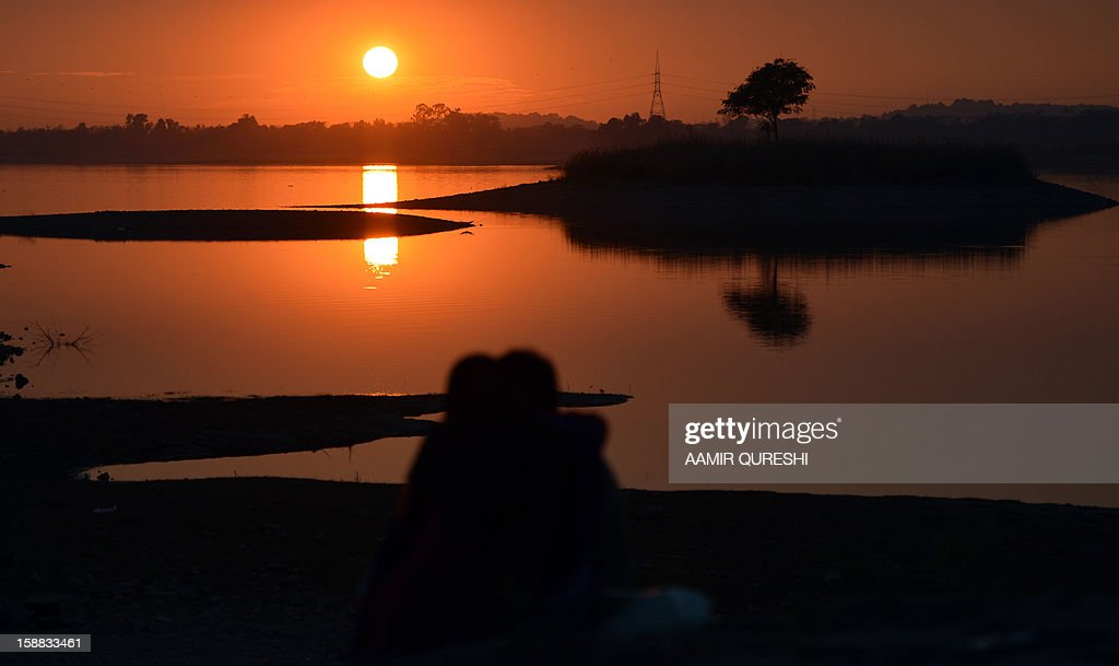 A Pakistani couple looks at the last sunset of 2012 at a lake view point in Islamabad on December 31, 2012. Sydney will kick off a wave of dazzling firework displays welcoming in 2013, from Dubai to Moscow and London, with long-isolated Yangon joining the global pyrotechnics for the first time. AFP PHOTO/ Aamir QURESHI