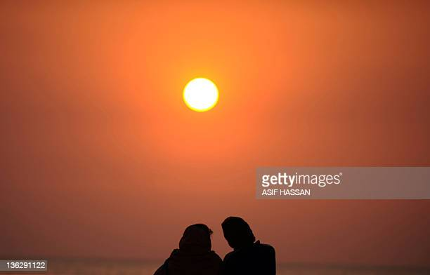 A Pakistani couple looks at the last sunset of the year 2011 at the Clifton beach in Karachi on December 31 2011 AFP PHOTO / ASIF HASSAN