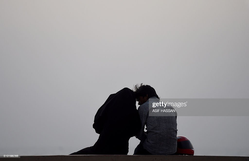 A Pakistani couple sits on a beach on Valentine's Day in Karachi on February 14, 2016. AFP PHOTO / Asif HASSAN / AFP / ASIF HASSAN