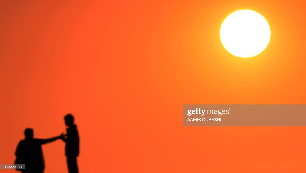 A Pakistani couple watch the last sunset of 2012 at a lake view point in Islamabad on December 31, 2012. Sydney will kick off a wave of dazzling firework displays welcoming in 2013, from Dubai to Moscow and London, with long-isolated Yangon joining the global pyrotechnics for the first time. AFP PHOTO/ Aamir QURESHI