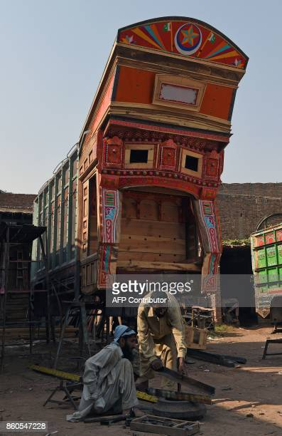 Pakistani craftsmen prepare a truck body before apply colourful decorations onto a goods truck at a workshop in Peshawar on October 12 2017 MAJEED