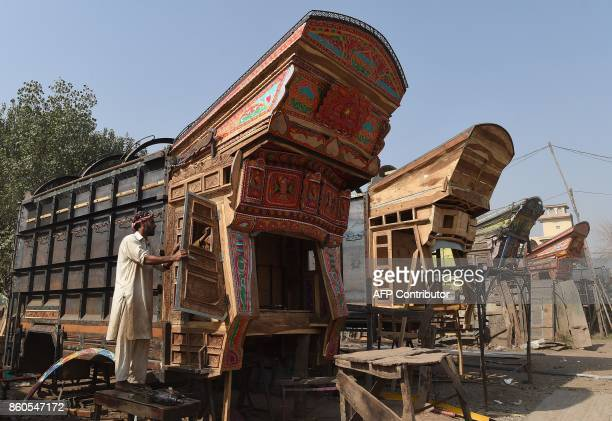 A Pakistani craftsmen prepares a truck body before apply colourful decorations onto a goods truck at a workshop in Peshawar on October 12 2017 MAJEED