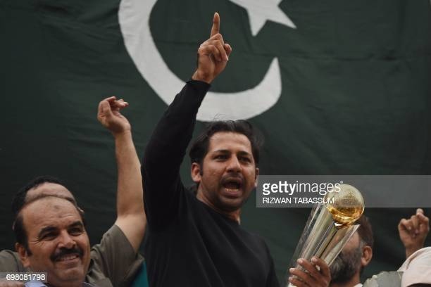 TOPSHOT Pakistani cricket captain Sarfaraz Ahmed acknowledges fans as he holds the Champions Trophy following his arrival from London in Karachi on...