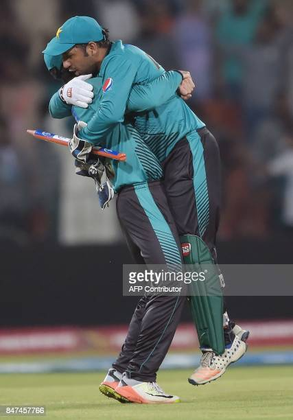 Pakistani cricket captain Sarfraz Ahmad celebrates with teammate Ahmed Shahzad after winning the third and final Twenty20 International match against...