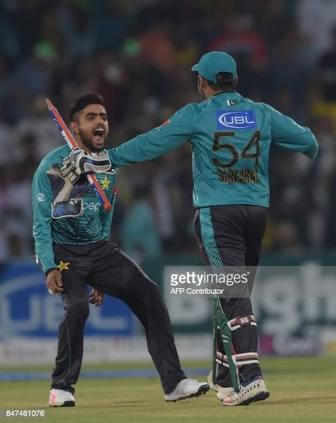 Pakistani cricket captain Sarfraz Ahmad celebrates with teammate Babar Azam after winning the third and final Twenty20 International match against...
