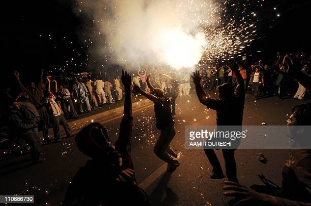 Pakistani cricket fans dance in celebration on a street in Islamabad on March 23 after Pakistan won a quarterfinal Cricket World Cup tournament match...