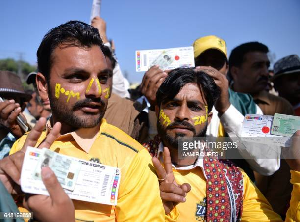 Pakistani cricket supporters of Peshawar Zalmi hold their match tickets as they queue at an entry gate of The Gaddafi Cricket Stadium in Lahore on...