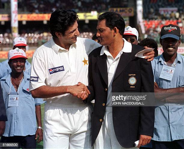 Pakistani cricket team captain Wasim Akram and his Indian counterpart Mohammad Azharuddin shake hands after the toss on the cricket pitch at...