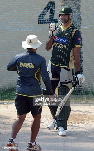 Pakistani cricket team coach Waqar Younis speaks with player Mohammad Irfan during a practice session at the Sharjah cricket stadium in Sharjah on...