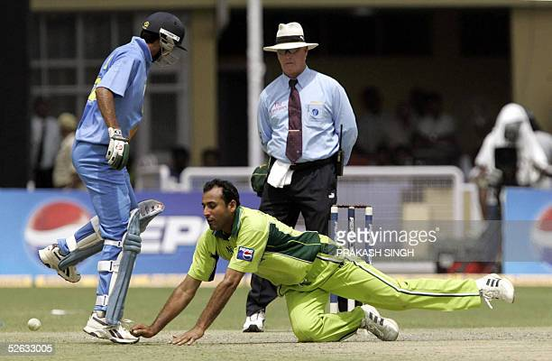 Pakistani cricketer Arshad Khan is watched by Indian batsman Mohammed Kaif and umpire Rudi Koertzen as he attempts to field a ball during the fifth...