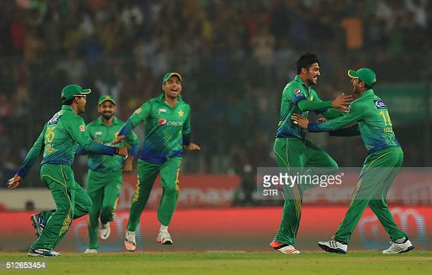 Pakistani cricketer Mohammad Amir celebrates with a teammate after the dismissal of the Indian cricketer Suresh Raina during the match between India...