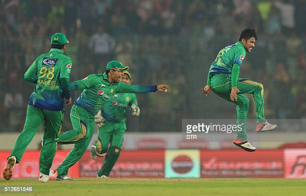 Pakistani cricketer Mohammad Amir celebrates with his teammates after the dismissal of the Indian cricketer Suresh Raina during the match between...